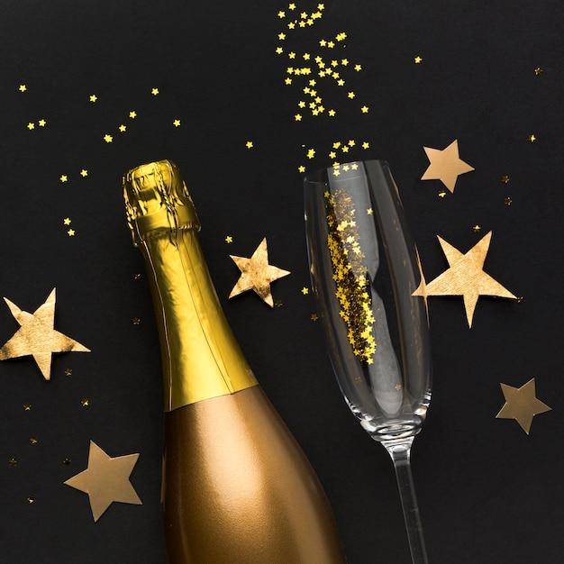 Bouteille de champagne avec verre et confettis
