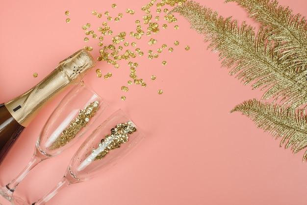 Bouteille de champagne, verres et branches dorées avec des confettis dorés