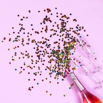 Bouteille de champagne, verres et confettis colorés or sur surface rose