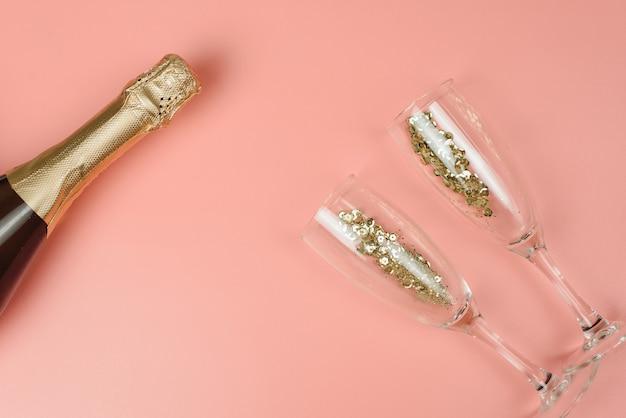 Bouteille de champagne et verres à vin avec des confettis dorés sur un pastel rose