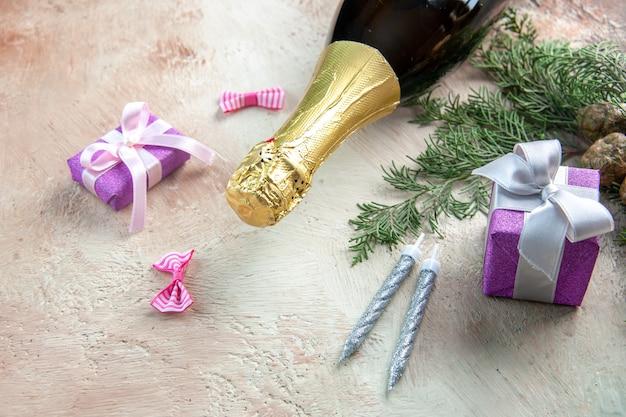 Bouteille de champagne vue de face avec de petits cadeaux sur fond clair