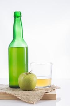 Bouteille de cidre asturien avec verre et pomme.