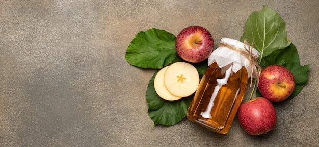 Bouteille de cidre de pomme entourée de feuilles de pomme et de pommes, vue de dessus