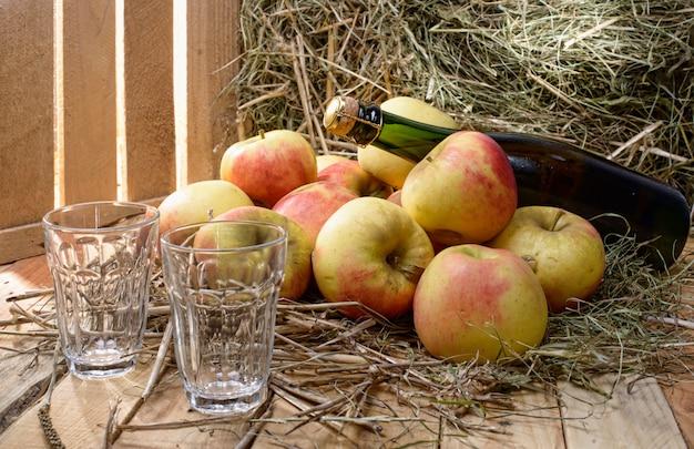 Bouteille de cidre avec quelques pommes et paille
