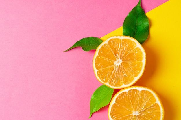 Bouteille cosmétique avec des agrumes en tranches sur fond rose vif