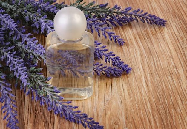 Bouteille avec cosmétique biologique et fleurs de lavande sur table en bois.