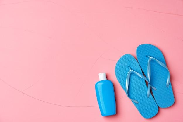 Bouteille cosmétique bleue avec crème solaire et tongs sur fond rose