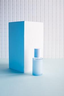 Bouteille cosmétique et cube blanc sur fond bleu, image maquette