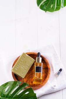 Bouteille cosmétique avec du sérum ou de l'acide hyaluronique et du savon d'olive sur une plaque en bois, feuille de palmier, sur une serviette blanche