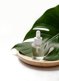 Bouteille cosmétique avec feuille verte sur blanc