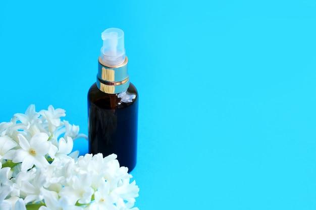Bouteille cosmétique à fleurs sur fond bleu