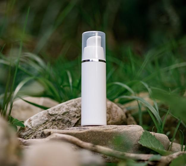 Une bouteille cosmétique se dresse sur une pierre. composition naturelle