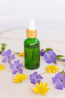 Bouteille cosmétique verte avec pipette sur une surface blanche avec des fleurs