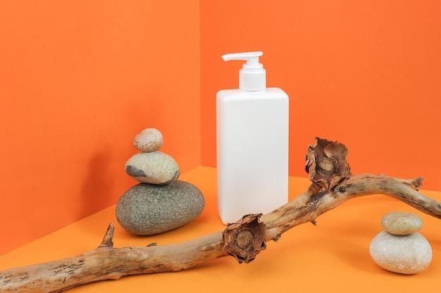 Une bouteille cosmétique vierge blanche avec distributeur, roches, bâton en bois avec des fleurs séchées dans un coin sur orange