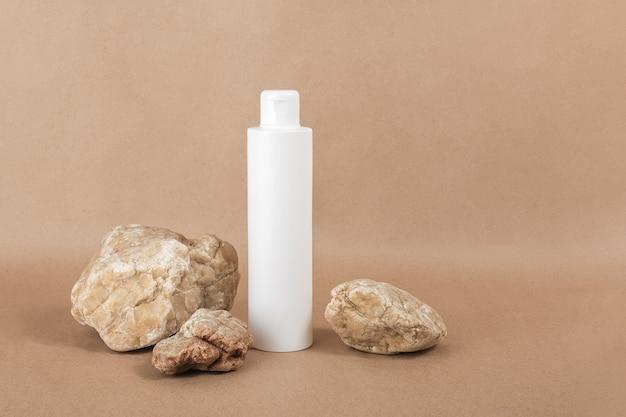 Bouteille cosmétique vierge blanche avec fond crème, lotion hydratante ou shampoing sur fond de papier kraft beige. concept cosmétique de spa bio naturel vue de face.