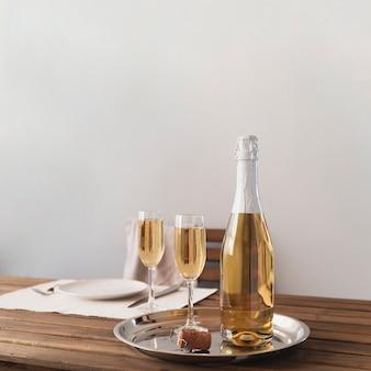 Bouteille avec des coupes à champagne sur un plateau