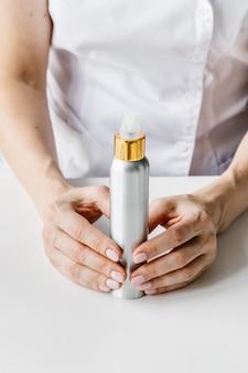 Bouteille de crème blanche et dorée dans la main de la femme. cosmétologue détenant un produit de soin de spin.
