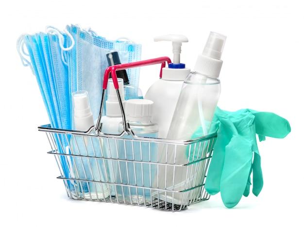 Bouteille de crème, lotion, désinfectant ou savon liquide, gant en caoutchouc latex et masque de protection dans le panier sur tableau blanc