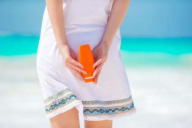 Bouteille de crème solaire closeup dans des mains féminines sur la plage