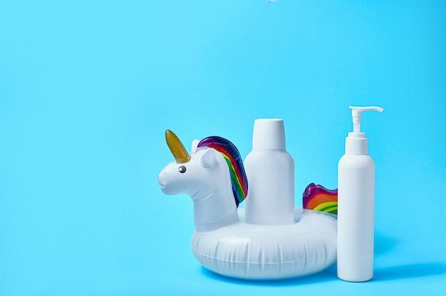 Bouteille de crème solaire avec jouet de piscine gonflable licorne blanche sur fond bleu concept minimal créatif