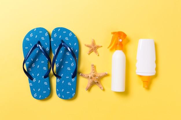 Bouteille de crème solaire ou spray corporel sur fond jaune vue de dessus à plat avec espace de copie. concept de voyage de vacances de vacances avec des accessoires de plage de mer.