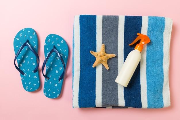 Bouteille de crème solaire ou spray corporel sur fond rose vue de dessus à plat avec espace de copie. concept de voyage de vacances de vacances avec des accessoires de plage de mer.
