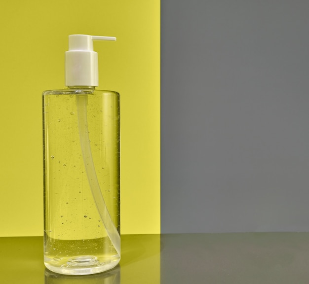 Bouteille de désinfectant pour les mains isolé sur un fond jaune et gris moderne.