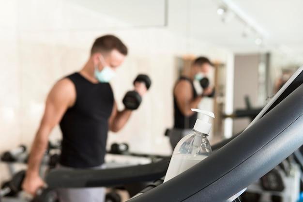 Bouteille de désinfectant pour les mains reposant sur un équipement de gym avec homme défocalisé travaillant