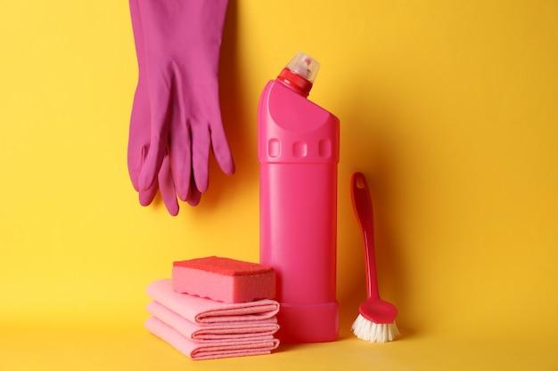 Bouteille de détergent et de produits de nettoyage sur fond jaune, espace pour le texte