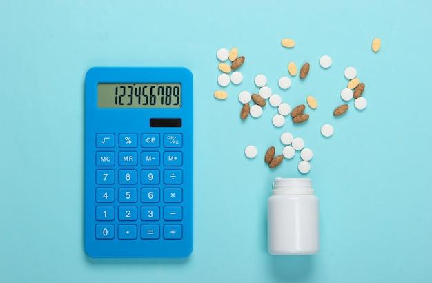 Bouteille avec différentes pilules et calculatrice sur un bleu