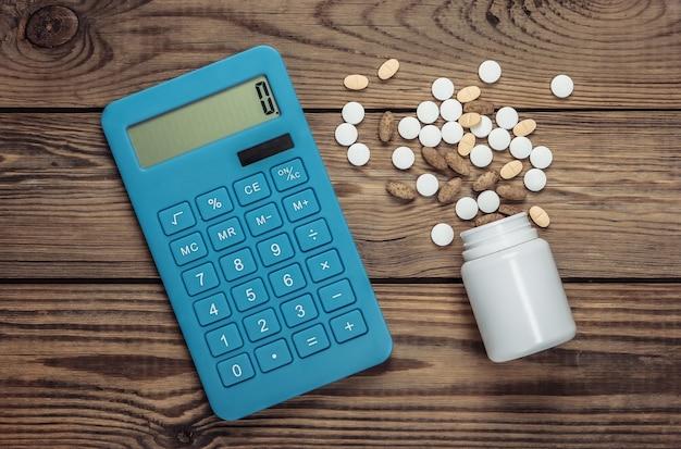 Bouteille avec différentes pilules et calculatrice sur table en bois