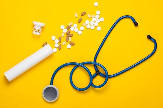 Bouteille avec différentes pilules et un stéthoscope sur un jaune
