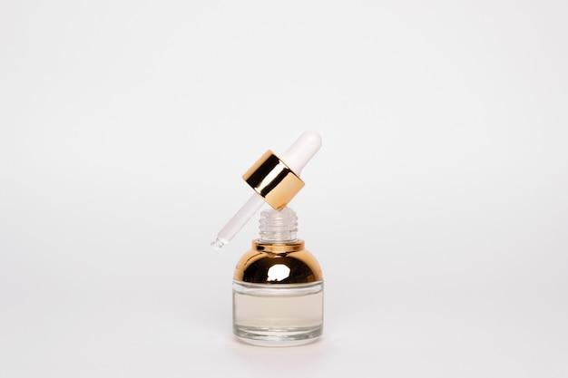 Bouteille dorée transparente avec pipette et acide hylauronique sur fond blanc