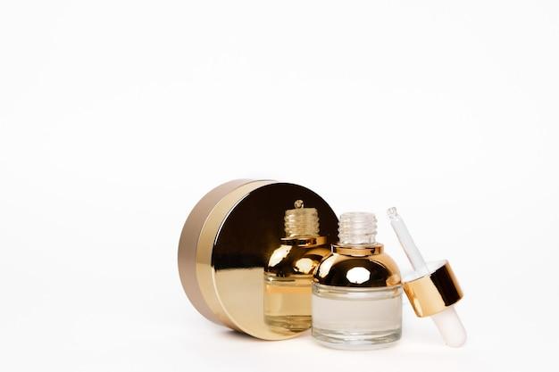 Bouteille dorée transparente avec pipette et contenant de crème arrondie or sur fond blanc