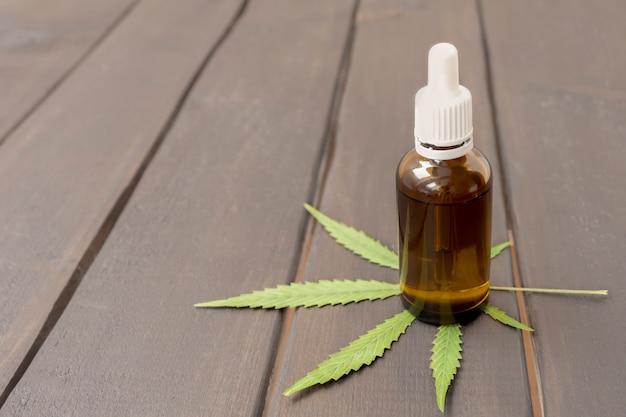 Bouteille avec dosage de gouttelettes de concentré d'huile de cbd à base de plantes médicinales sur fond de bois