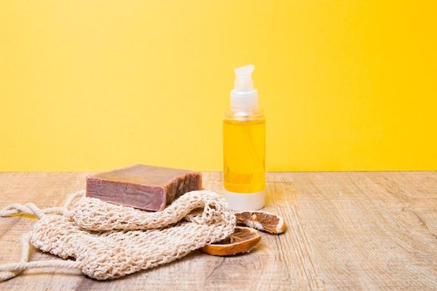 Bouteille avec du beurre corporel et du savon au cacao sur un gant de toilette tricoté, du savon maison et des tranches d'orange séchée sur une table en bois