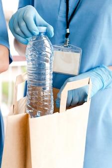 Bouteille d'eau ajoutée au sac de don