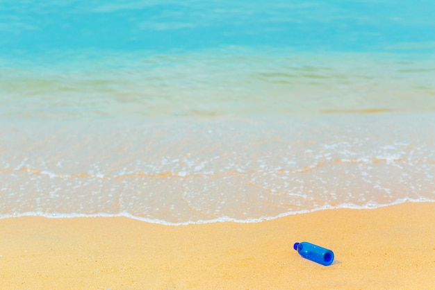 Bouteille d'eau bleue sur la plage avec la toile de fond de la mer bleue
