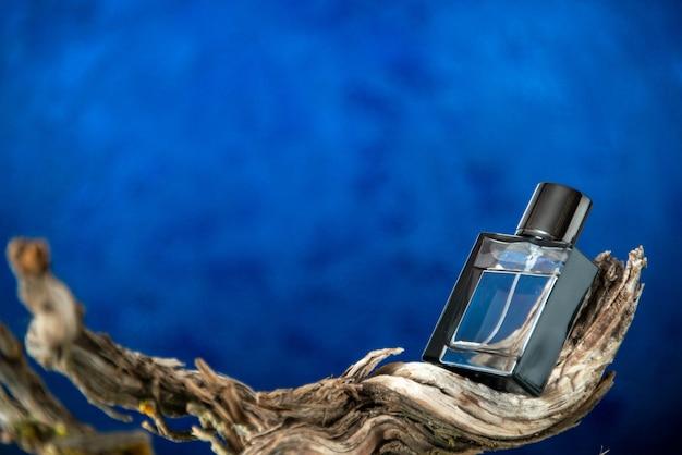 Bouteille d'eau de cologne vue de face sur une branche de bois pourri sur fond bleu foncé lieu de copie