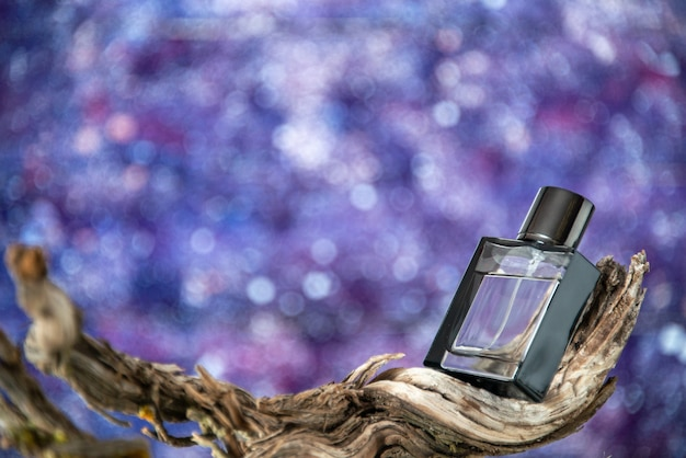 Bouteille d'eau de cologne vue de face sur une branche de bois pourri isolé sur fond aquarelle violet