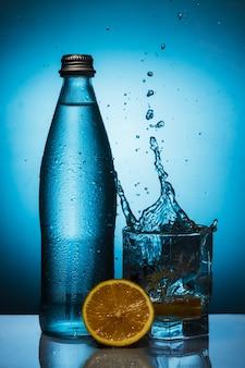Bouteille d'eau embuée avec spray dans un verre et citron