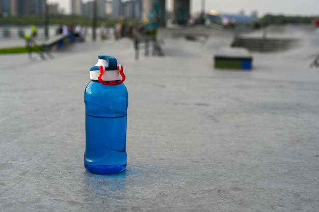 Bouteille d'eau sur le fond d'un parc extrême. fermer. le skate park, rollerdrome, rampes quarter et half pipe. sport extrême, culture urbaine des jeunes pour l'activité de rue des adolescents.