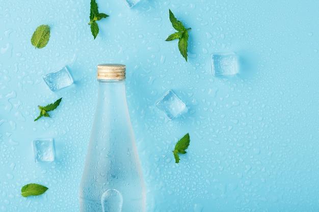 Une bouteille d'eau glacée, des glaçons, des gouttes et des feuilles de menthe sur bleu.