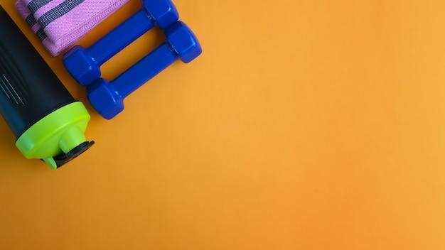 Bouteille d'eau et haltères sur fond jaune.