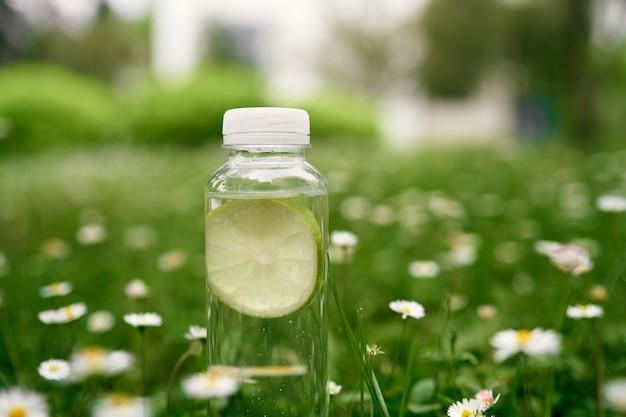 Bouteille d'eau sur l'herbe verte parmi les marguerites