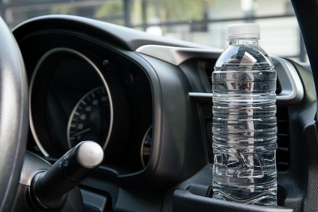 Bouteille d'eau en plastique laissée dans le véhicule lors du stationnement sur un parking extérieur, une bouteille en plastique contenant de l'eau est à l'origine d'un incendie et d'une brûlure dans une voiture. évitez de vous garer sur les terrains extérieurs.