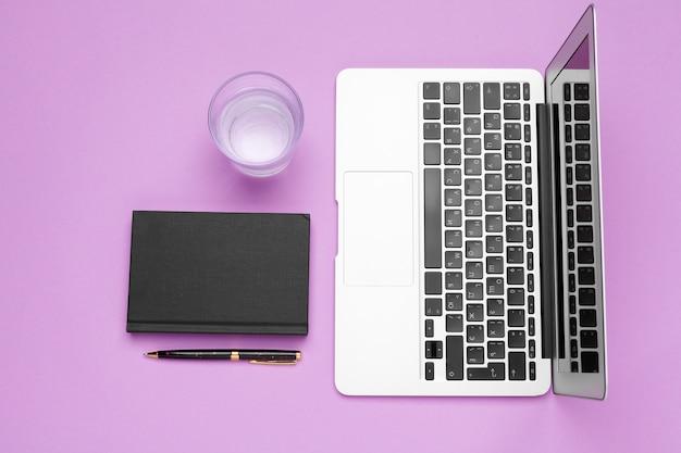 Bouteille d'eau sur la table de bureau près d'un ordinateur portable