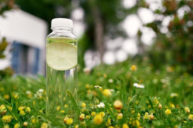 Bouteille d'eau avec une tranche de citron à l'intérieur sur un pré vert