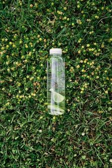 Une bouteille d'eau avec une tranche de citron vert se trouve sur l'herbe verte parmi les fleurs sauvages