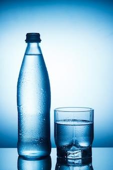 Bouteille d'eau et verre sur fond bleu